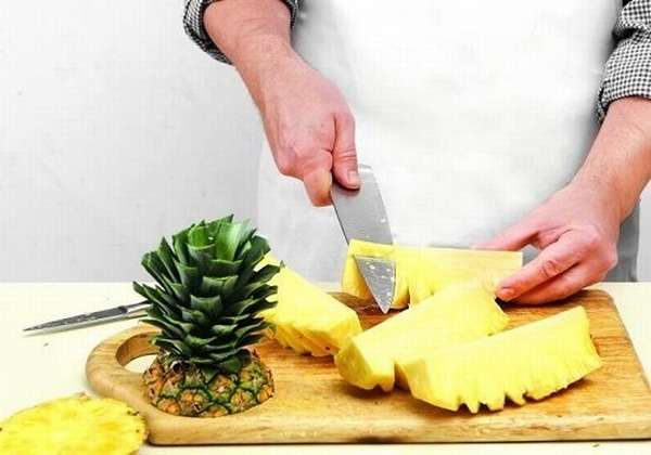 Мужчина разделывает ананас